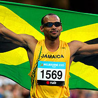 Maurice Wignall proudly displays the Jamaican flag after winning the gold medal at the 110m Men's Hurdles final.